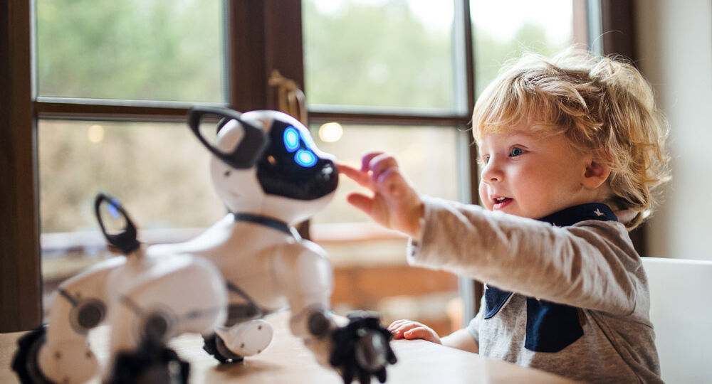A cute toddler boy standing indoors at home, playing with robotic dog.